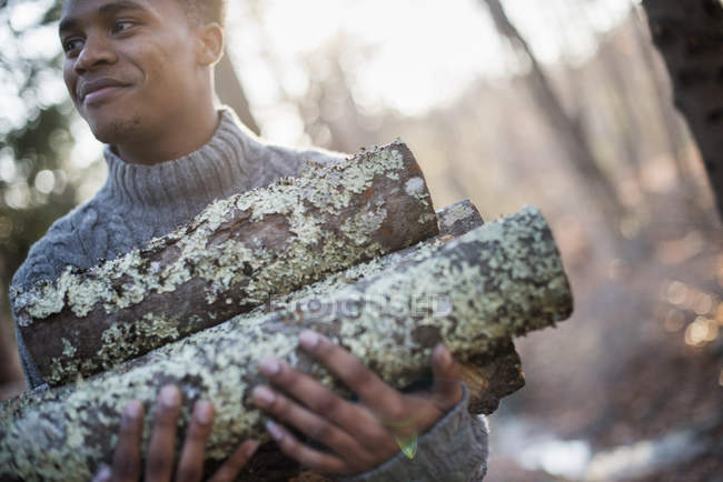 Man carrying firewood in forest — Stock Photo