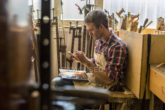 Furniture restorer sitting using a smart phone — Stock Photo