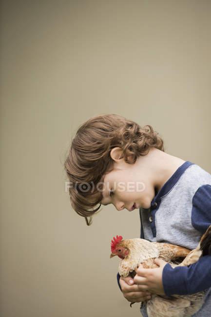 Мальчик держит курицу — стоковое фото