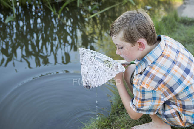 Boy outdoors with a fishing net — Stock Photo