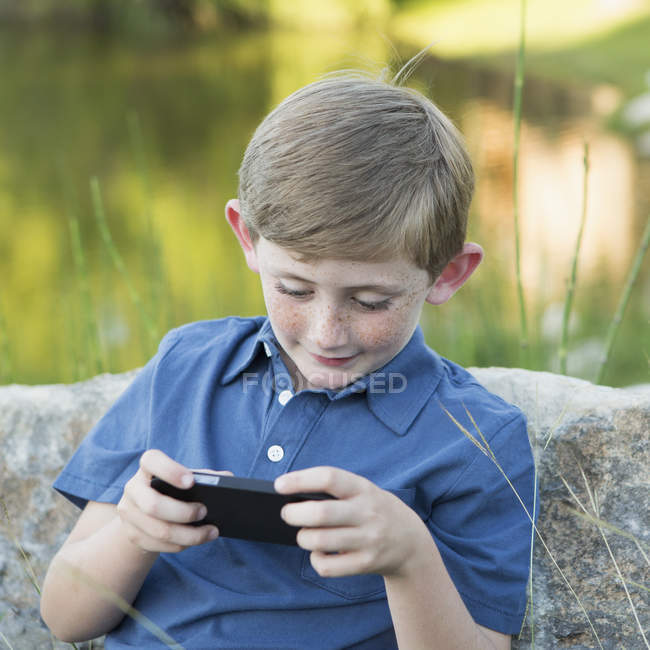 Boy using a handheld electronic game. — Stock Photo