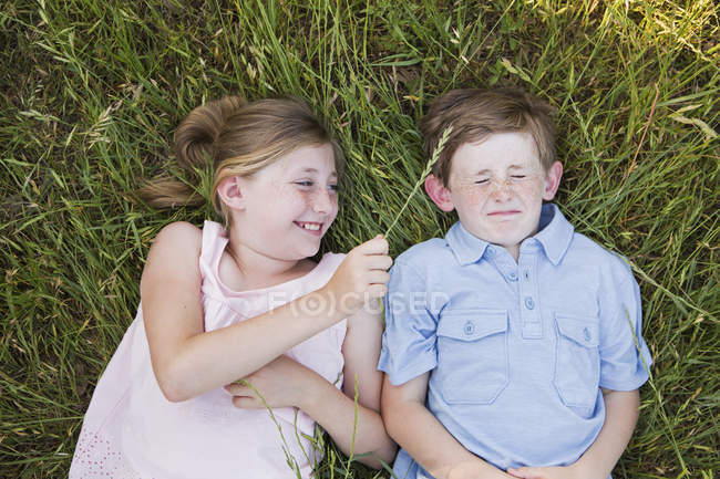 Brother and sister lying on the grass — Stock Photo