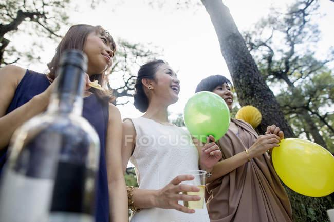 Amigos en la fiesta al aire libre en el bosque - foto de stock
