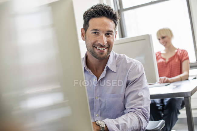 People seated at desks using computers. — Stock Photo