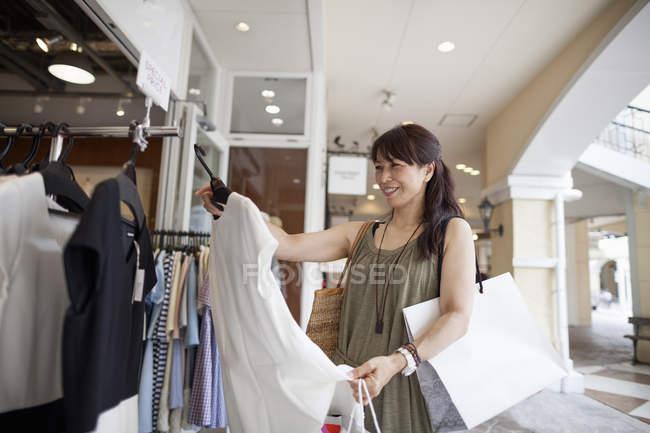 Mujer mirando ropa - foto de stock