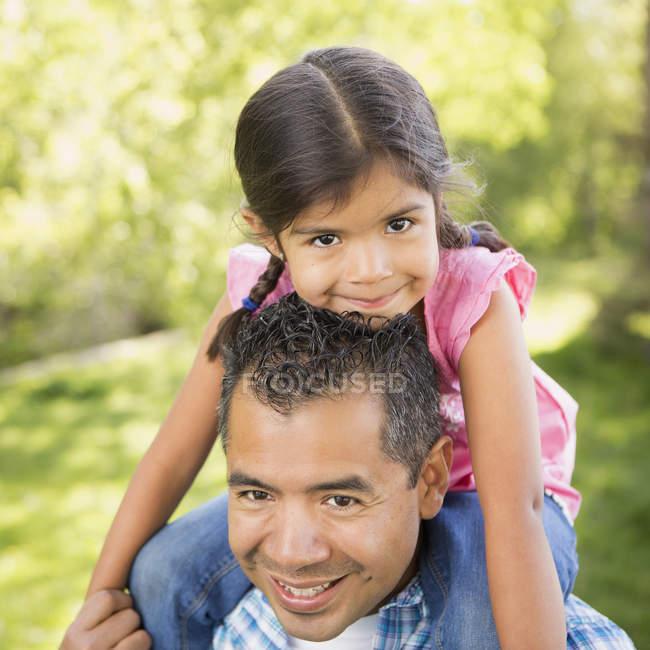 Man giving daughter a piggyback ride — Stock Photo