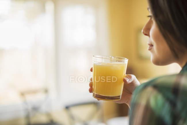 Mulher segurando suco de laranja — Fotografia de Stock