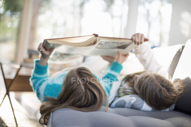 Two girls lying on sofa on their back — Stock Photo