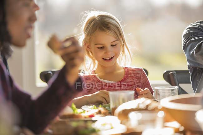 Adulti e bambini seduti attorno a un tavolo — Foto stock