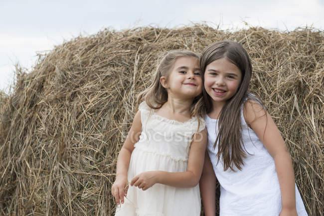 Ragazze in piedi vicino a una grande balla di fieno — Foto stock