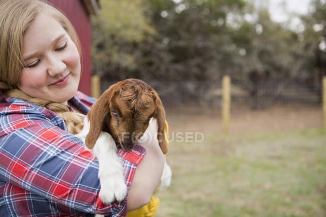 Girl cuddling goat. — Stock Photo