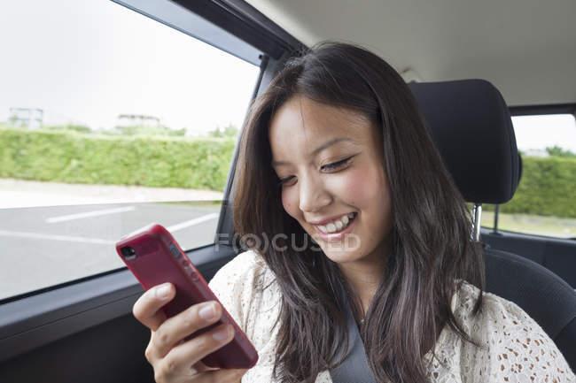 Жінка користується смартфоном у машині. — стокове фото