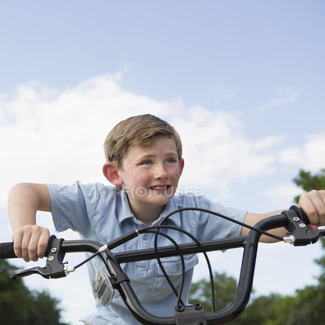 Ragazzo appoggiato al manubrio di una bicicletta . — Foto stock