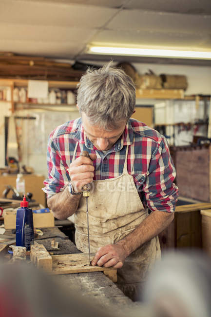 Furniture restorer works on a workbench — Stock Photo