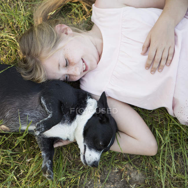 Girl hugging a black and white dog — Stock Photo
