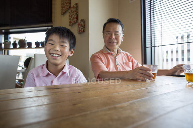 Man and boy sitting at dining table — Stock Photo