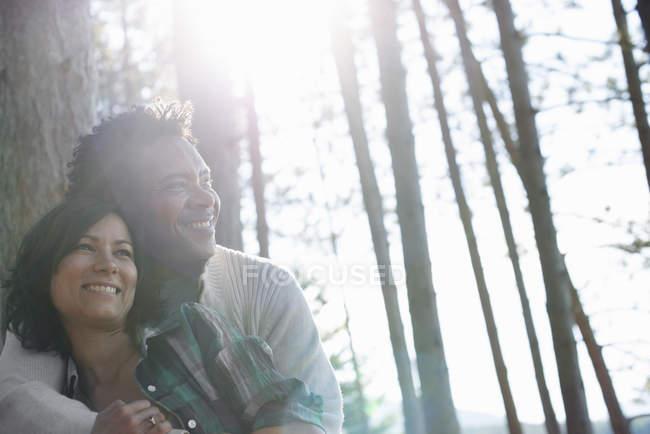 Пара, обнимая в тени дерева — стоковое фото