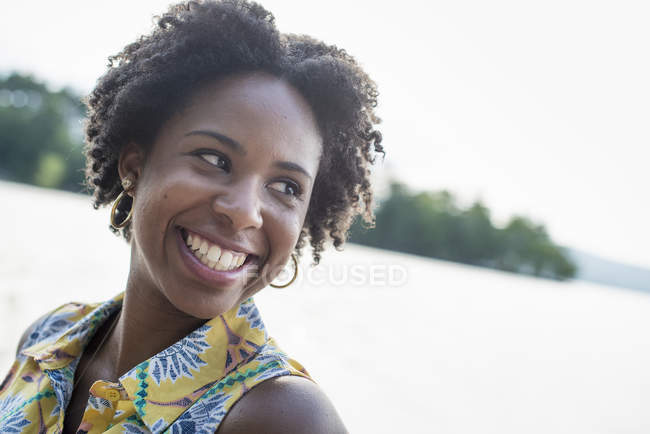 Woman laughing on a lake shore — Stock Photo