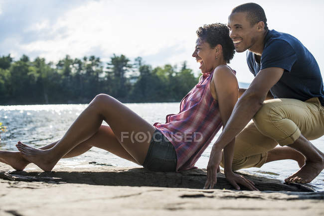 Couple close together by a lake — Stock Photo