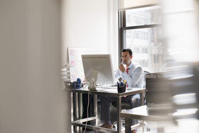 Man seated at a desk in an office — Stock Photo