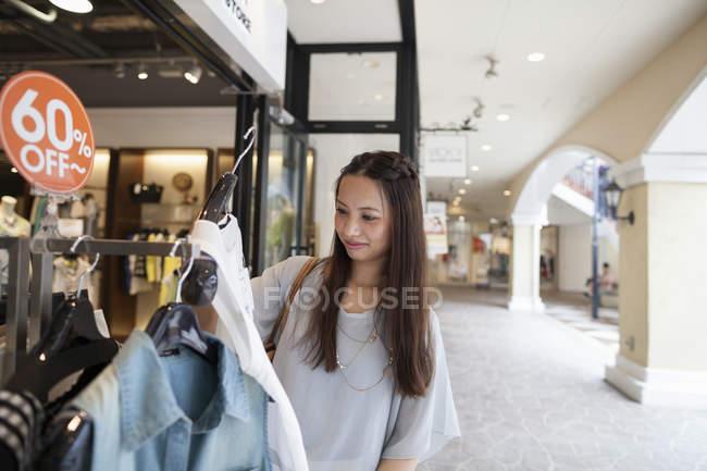 Donna che guarda i vestiti — Foto stock