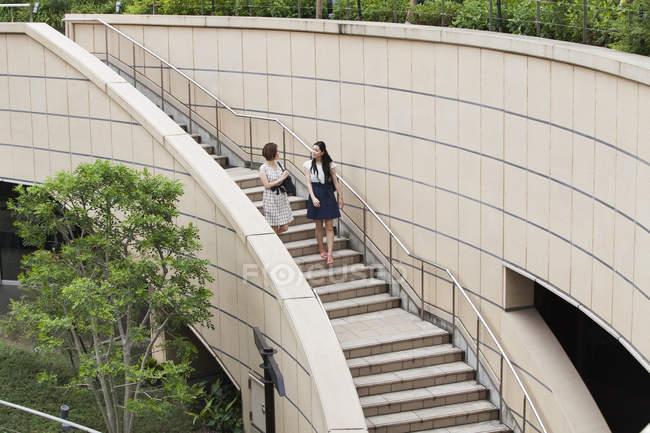 Dos mujeres en escalones en el complejo comercial - foto de stock