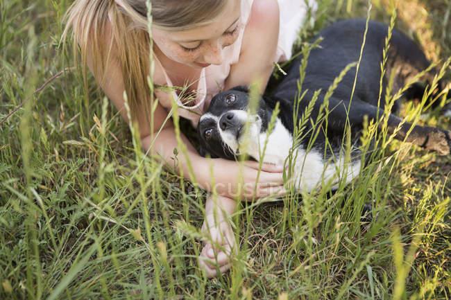 Девушка обнимает черно-белую собаку — стоковое фото