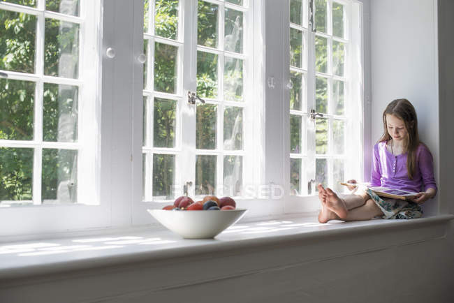 Girl sitting by a window — Stock Photo