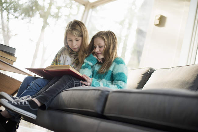 Two girls reading a book on sofa — Stock Photo