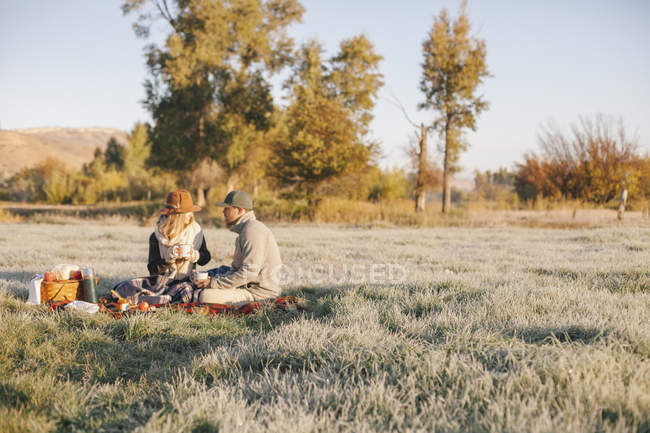 Man and woman having a winter picnic — Stock Photo