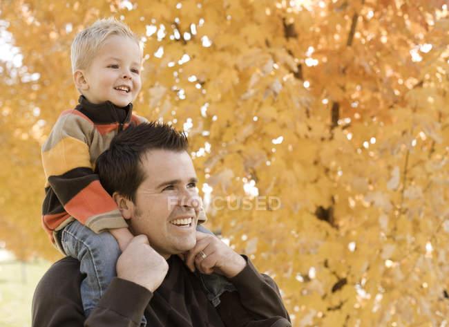 Padre e figlio sotto foglie d'autunno . — Foto stock