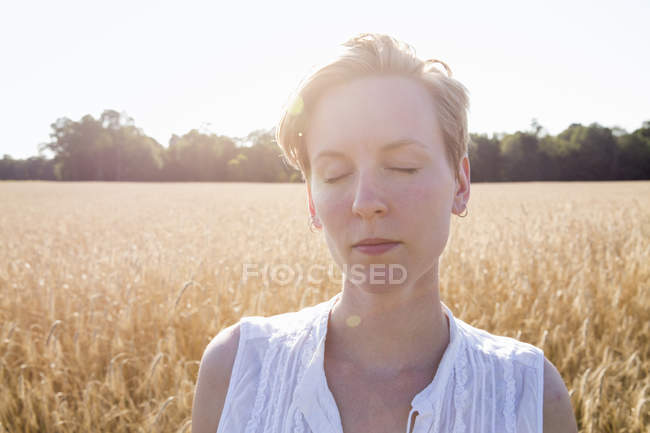Young woman standing in a wheat field — Stock Photo