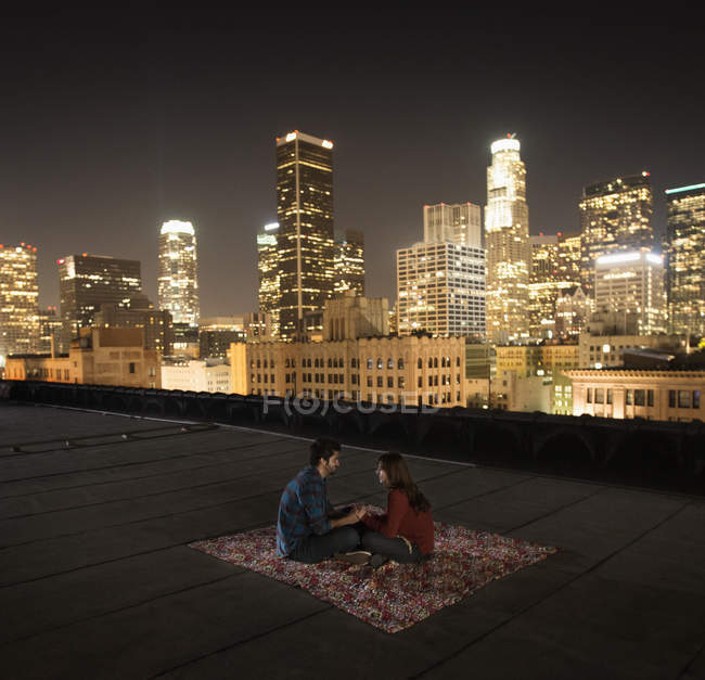 Couple sitting on a rug on a rooftop — Stock Photo