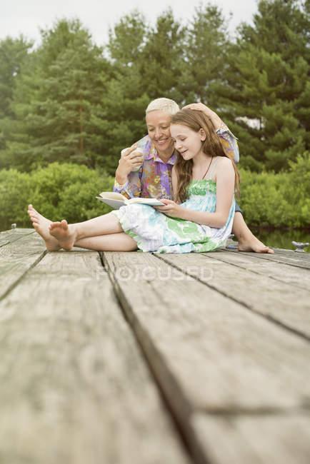 Ребенка, чтение рядом с зрелой женщиной — стоковое фото