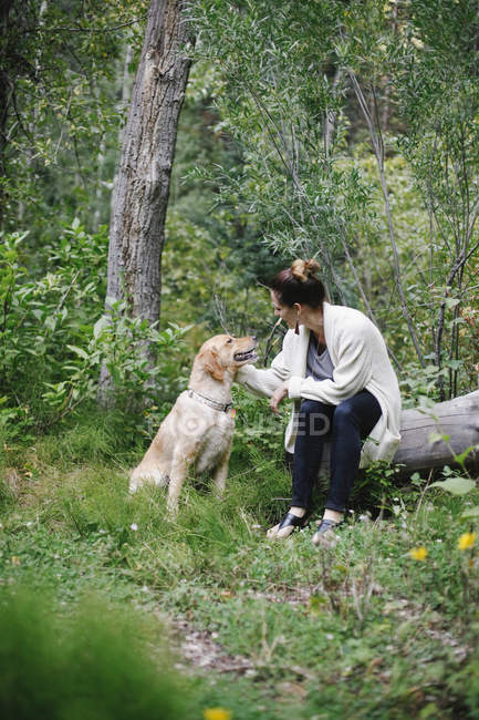Woman petting her dog — Stock Photo