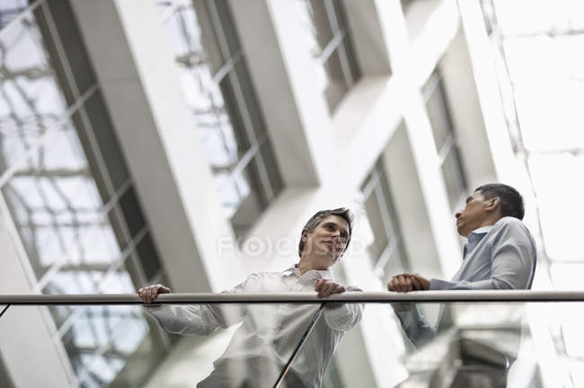 Business colleagues standing by a railing — Stock Photo