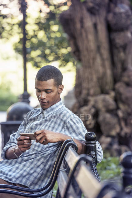 Man using his smart phone on bench — Stock Photo