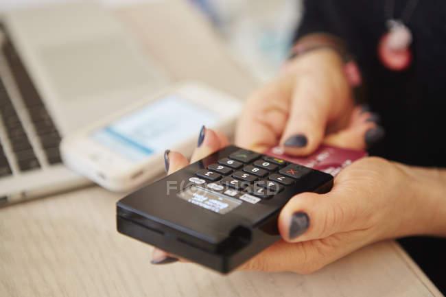 Manos sosteniendo un lector de tarjetas de crédito - foto de stock