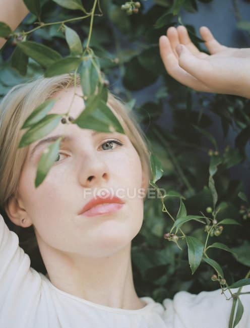 Woman looking wistfully through leaves. — Stock Photo