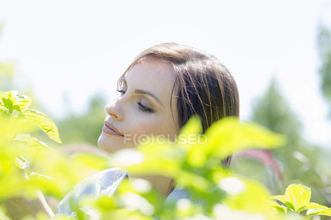 Woman surrounded by green plants — Stock Photo