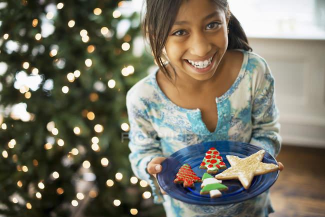 Chica sosteniendo la placa con las galletas de Navidad - foto de stock