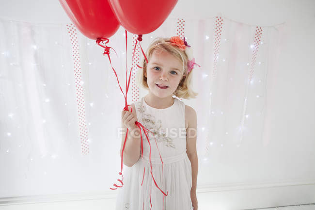 Young girl holding red balloons — Stock Photo
