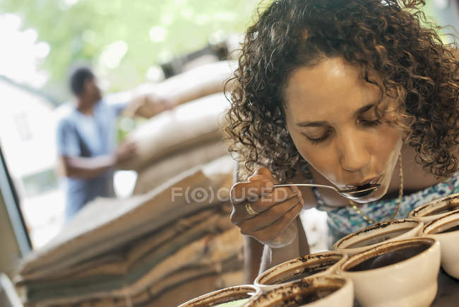Woman sampling in a coffee processing shed — Stock Photo