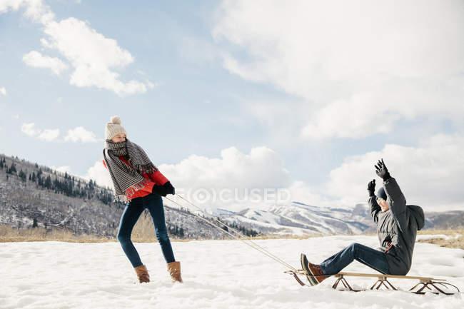 Дівчина потягнувши її брат на санях — стокове фото