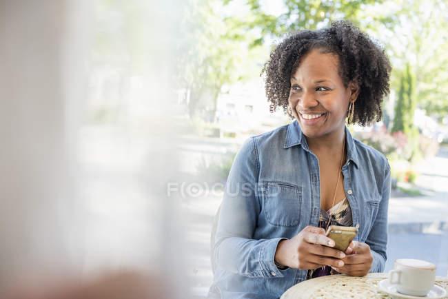 Frau mit Smartphone in einem Café — Stockfoto
