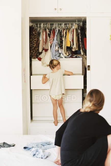 Дівчина шукає одягу в комод — стокове фото