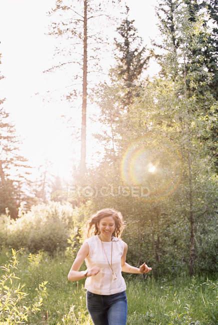Жінка проходить через сонячної ліс. — стокове фото