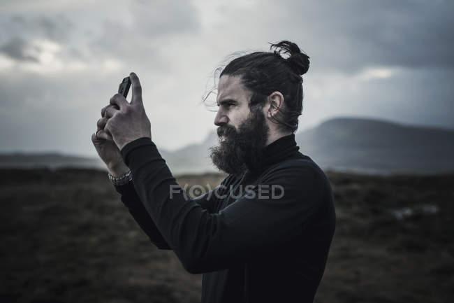 Uomo che scatta una foto con un telefono — Foto stock