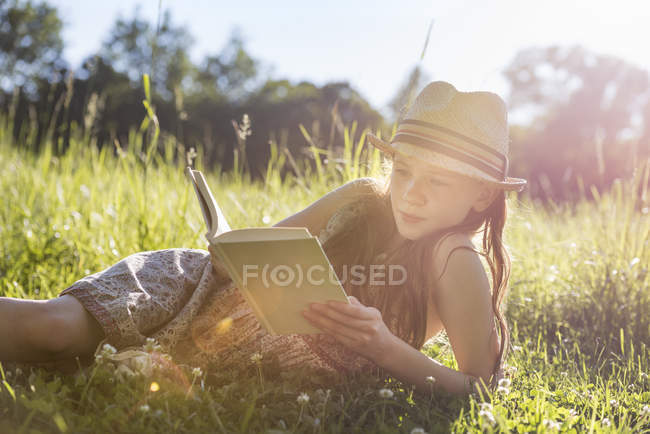 Mädchen liegt im Gras und liest ein Buch — Stockfoto