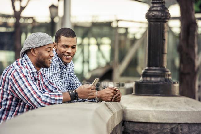 Hombres apoyados en un parapeto junto a un puente - foto de stock